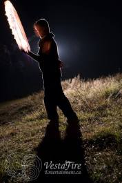 backlit fire performer with fire sword in Errington