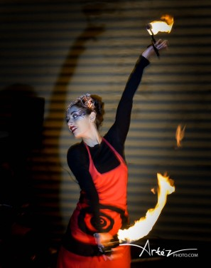 Beautiful fire dancer with palm candles