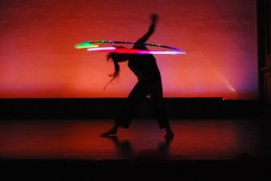 young hula hoop performer doing duck out