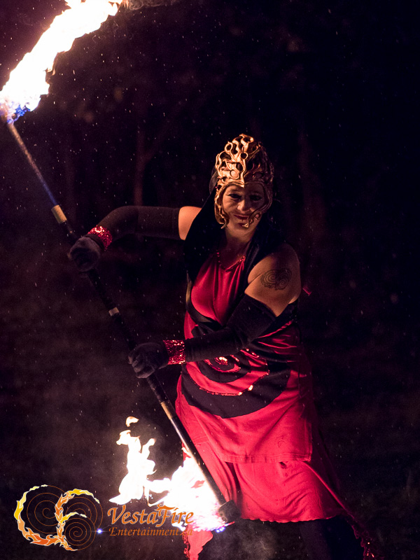 Fire performer dances with contact Staff